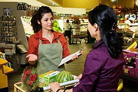 Hispanic clerk helping shopper in grocery store