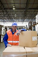 African worker leaning on boxes in warehouse