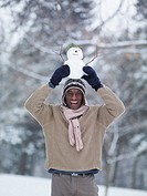 African man balancing miniature snowman on head