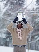 African man balancing miniature snowman on head