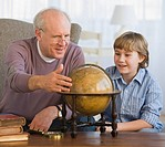 Grandfather and grandson looking at globe