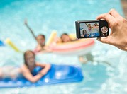 Person photographing girls in swimming pool