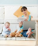 Mother working next to baby playing on floor