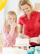 Mother and daughter next to birthday cake