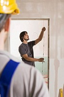 Man measuring door with folding rule