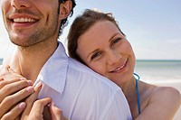Germany, Baltic sea, Young couple embracing on beach, smiling, portrait