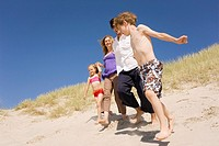 Germany, Baltic sea, Family running down beach dune