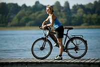 Germany, Bavaria, Tegernsee, Woman with mountain bike on landing stage
