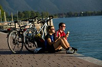Germany, Bavaria, Tegernsee, Couple with mountain bikes eating ice cream (thumbnail)