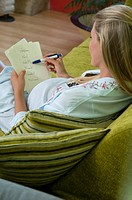 Pregnant woman writing down babys names