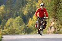 Austria, Tyrol, Ahornboden, Mountainbiker riding across highway