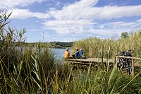 Italy, Tuscany, Lago dell'Accesa, Mountainbikers taking a break on the lakefront