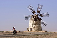 Spain, The Canary Islands, Man mountain biking, windmill in background