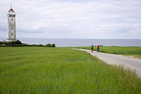 Denmark, Fuenen, Couple mountainbiking across farm track, lighthouse in background