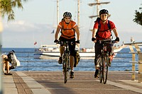 Spain, The Canary Islands, Gran Canaria, Couple mountain biking across promenade
