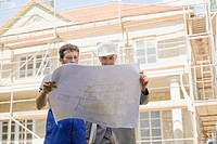 Architect and Construction worker looking at construction plan