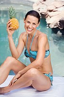 Young woman in bikini holding ananas