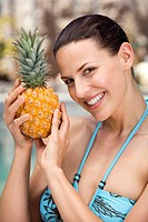 Young woman in bikini holding ananas, portrait