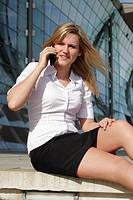 Frau sitzt vor Büro und telefoniert