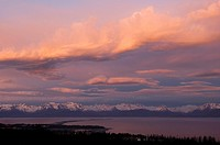 Cumulonimbus clouds over Kenai Mtns w/the lights of Homer Spit @ sunset Kenai Peninsula Summer Evening