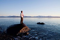 Woman stands on rock at Bishops Beach viewing Kachemak Bay at Homer, Alaska