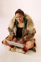 Native Alaskan Inupiat Woman in Wolf Fur Coat in Studio w/ laptop computer