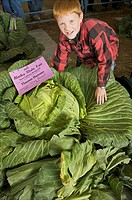 Young boy poses with his 69 pound cabbage at the Alaska State Fair, Palmer, Alaska