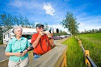 Senior couple photographs birds from a viewing deck at Creamer's Dairy near Fairbanks. Summer in Interior Alaska