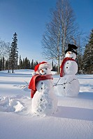 Snowmen in forest after making snow angel imprint in snow Alaska Winter