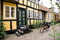Denmark, Fuenen, Couple mountain biking alongside timbered houses