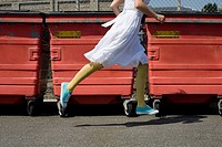 Woman running past wheelie bins