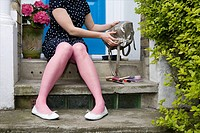 Woman emptying handbag on doorstep