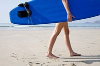 Woman carrying a surfboard on beach