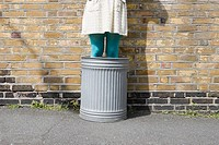 Woman standing in a dustbin