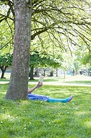 Woman reading a book behind a tree