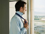 A businessman tying his tie