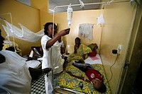 NURSE DISPENSING CARE Photo essay in a hospital in Congo. Pediatrics department. Nurse watchng the drip of rehydration glucose solution.