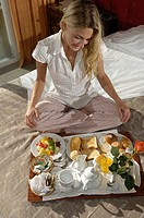 Girl sitting on the bed and breakfast.
