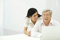 Senior man and mid-adult woman looking at laptop together, smiling