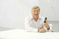 Senior man laughing, holding cell phone, looking at camera