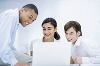 Young professionals looking at laptop computer together, smiling