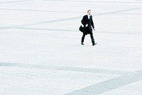 Businessman hurrying across public square (thumbnail)