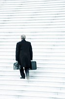 Businessman carrying two heavy bags slowly going up stairs outdoors