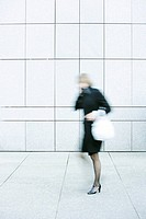 Businesswoman talking on phone while walking down sidewalk