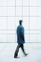 Man walking with hands in pockets down sidewalk (thumbnail)