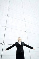 Woman standing with arms outstretched head back looking up (thumbnail)