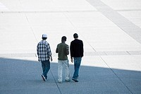 Three young men walking together across public square