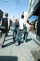 Young men walking NE along sidewalk on 8th Avenue in Chelsea, New York City, rear view