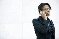 Businesswoman using cell phone, looking away (thumbnail)