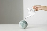 Hand holding watering can over small globe